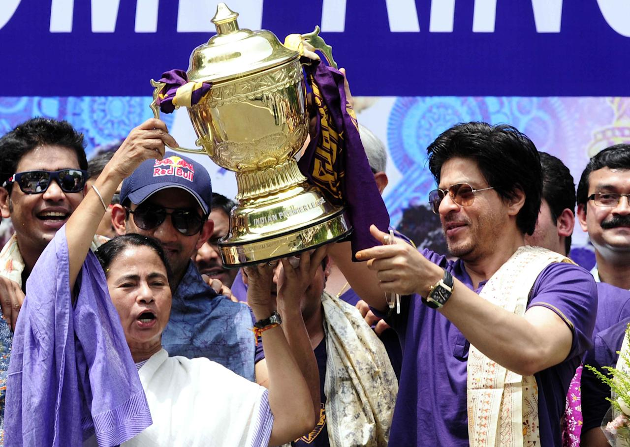 Chief minister of West Bengal, Mamata Banerjee (L) holds the IPL Twenty20 champion's trophy with Kolkata Knight Riders owner Shah Rukh Khan (R) during celebrations in front of the Writers Building in Kolkata on May 29, 2012.   Kolkata Knight Riders claimed victory in the annual IPL Twenty20 cricket tournament final on May 27, beating defending champions Chennai Super Kings by five wickets. AFP PHOTO/STR        (Photo credit should read STRDEL/AFP/GettyImages)
