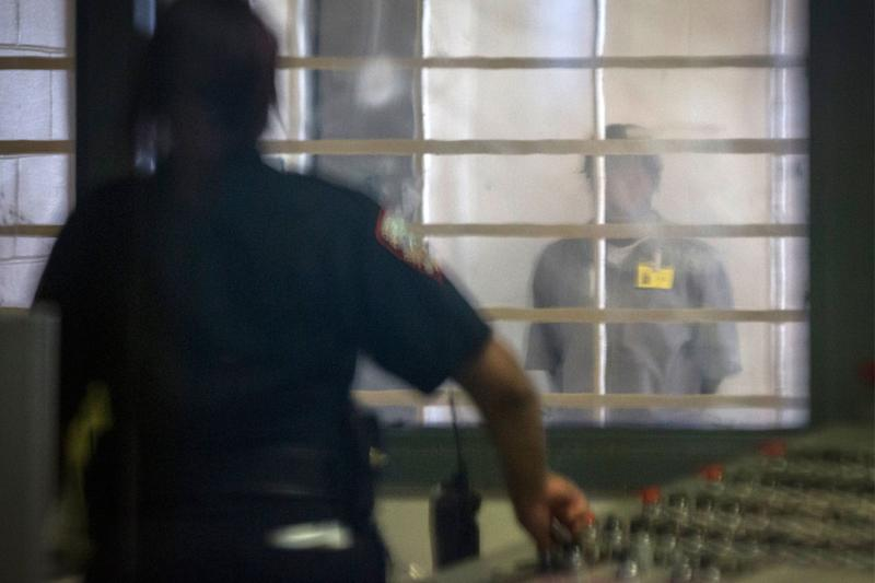 A prisoner looks at a corrections officer from behind several layers of glass and bars in the enhanced supervision housing unit at Rikers Island in New York on March 12, 2015. (Photo: Brendan McDermid/Reuters)