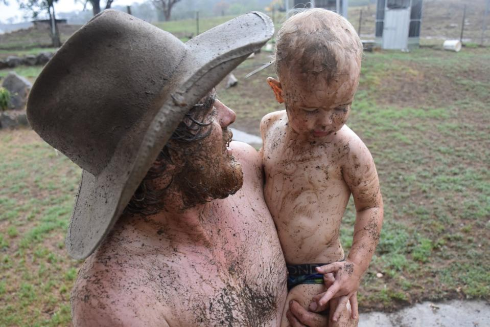 Wollomombi father and son Nick and Archie Saunders cover themselves in mud as rain falls.