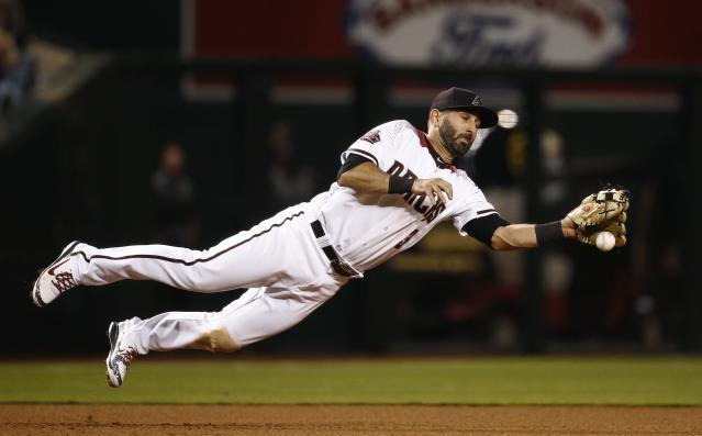 Arizona Diamondbacks third baseman Daniel Descalso knocks down a line drive hit by San Francisco Giants' Austin Jackson before throwing to second base to start a double play during the seventh inning of a baseball game Wednesday, April 18, 2018, in Phoenix. (AP Photo/Ross D. Franklin)