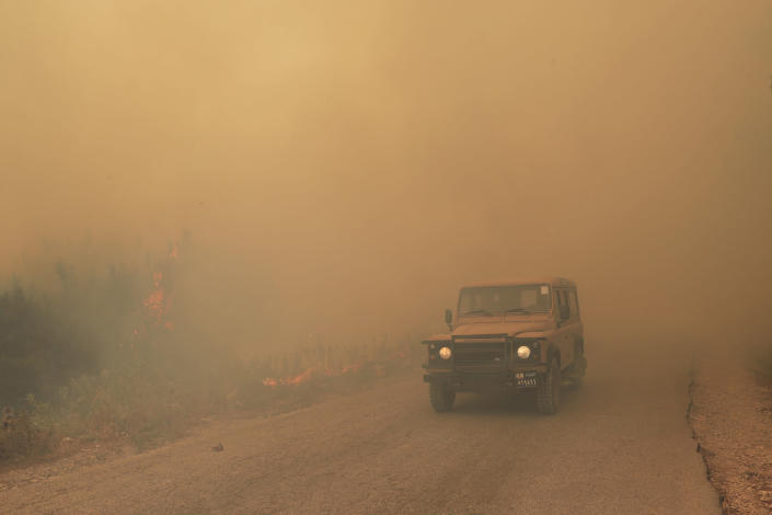 A Lebanese army vehicle drives past flames of a forest fire, at Qobayat village, in the northern Akkar province, Lebanon, Thursday, July 29, 2021. Lebanese firefighters are struggling for the second day to contain wildfires in the country's north that have spread across the border into Syria, civil defense officials in both countries said Thursday. (AP Photo/Hussein Malla)