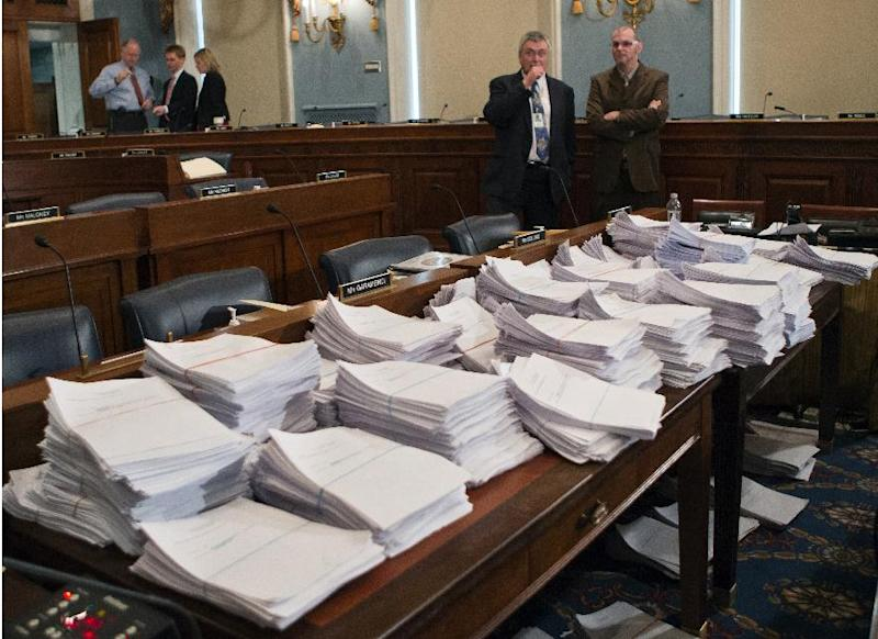 FILE - This May 15, 2013 file photo shows stacks of paperwork awaiting members of the House Agriculture Committee on Capitol Hill in Washington, as it meets to consider proposals to the 2013 Farm Bill. Conservative groups pressured rural-state Republicans - many representing agricultural districts - with radio ad campaigns to oppose the five-year $940-billion bill, calling its proposed cuts to food stamps too little. Democrats, whose districts mostly encompass urban areas home to food-stamp recipients, refused to budge on cuts they considered too deep. Each party was fearful of angering their core supporters. (AP Photo/J. Scott Applewhite, File)