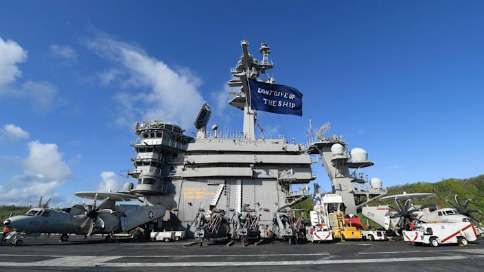 """The aircraft carrier USS Theodore Roosevelt flies a replica of Capt. Oliver Hazard Perry's """"Don't Give Up the Ship"""" flag, in Apra Harbor, Guam June 3, 2020."""