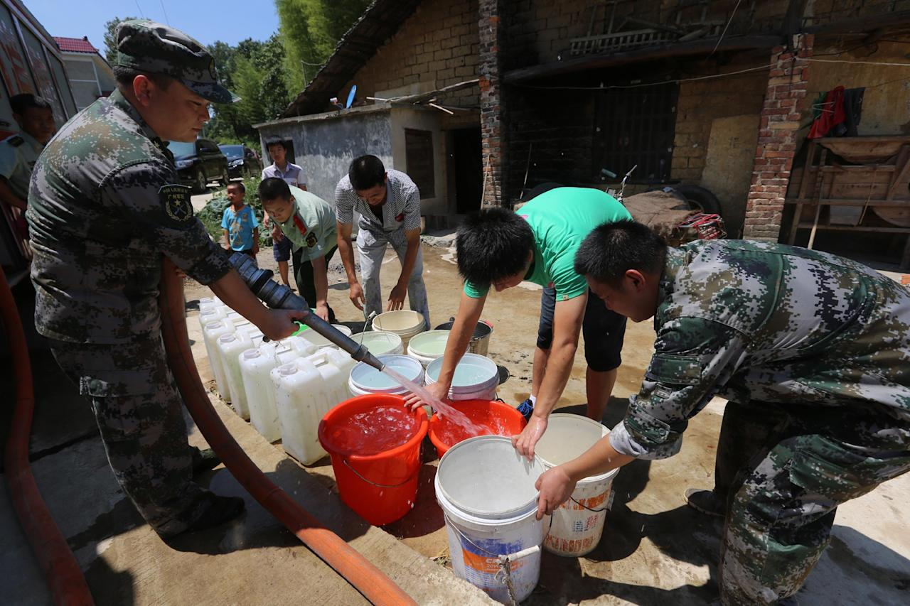 LOUDI, CHINA - JULY 31: (CHINA OUT) Villagers collect water from a military water truck at Qishi village on July 31, 2013 in Loudi, China. The drought has left 533,000 people short of drinking water in Hunan privince following little rainfall in July. (Photo by ChinaFotoPress/Getty Images)