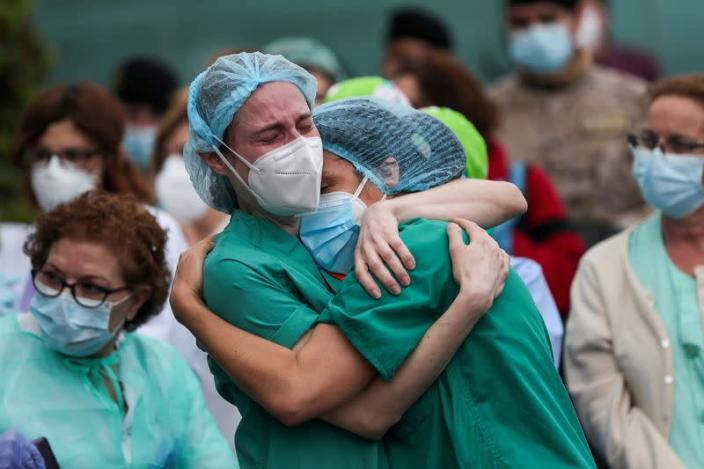 FILE PHOTO: Health workers wearing protective face masks react during a tribute for a co-worker who died in Leganes