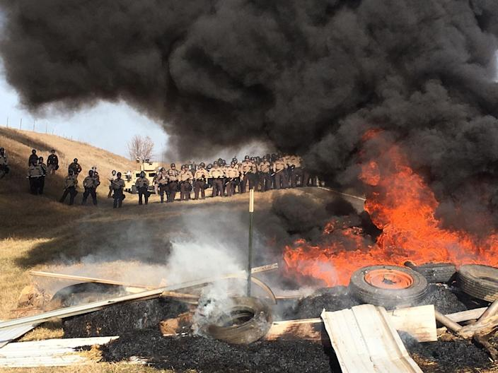 <p>Tires burn as armed soldiers and law enforcement officers stand in formation on Thursday, Oct. 27, 2016, to force Dakota Access pipeline protesters off private land where they had camped to block construction. (Photo: Mike McCleary/The Bismarck Tribune via AP) </p>