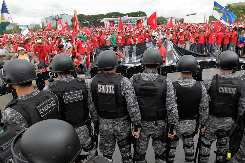 A shock battalion of the Military Police mounts barrier in front of the Planalto presidential palace during a March of the Landless Workers Movement in Brasilia, Brazil, Wednesday, Feb. 12, 2014. The Landless Workers Movement, one of the globe's biggest agrarian reform movements called the protest to demand that the government hand over more unused land to impoverished farmers who have none of their own. (AP Photo/Eraldo Peres)
