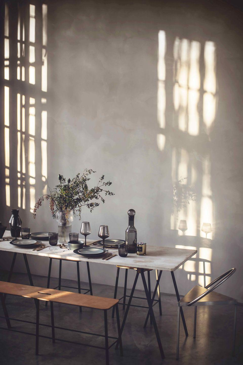 """<p>Let your tableware do the talking with beautiful smoky grey glass in clean shapes that lets the light shine through. Limited decoration required, this is all about simple, elegant styling, care of Our Food Stories.</p><p>'Trestle' <strong>table</strong>, approx £2,152; 'Triangolo' <strong>chairs </strong>in Steel, approx £904; 'Adam' <strong>bench</strong>, approx £603, all Frama (<u><a href=""""https://framacph.com/?gclid=Cj0KCQiAhs79BRD0ARIsAC6XpaUyvKUJWJXjLDnA7ilYbyFJv9zpEPNz1sd8dSCUTf0v1FmWsfQ_jRYaAhAUEALw_wcB"""" rel=""""nofollow noopener"""" target=""""_blank"""" data-ylk=""""slk:framacph.com"""" class=""""link rapid-noclick-resp"""">framacph.com</a></u>). <strong>Tableware</strong>, <strong>glassware</strong>, <strong>cutlery </strong>and <strong>glass vases</strong>, from a selection, H&M Home (hm.com)</p>"""