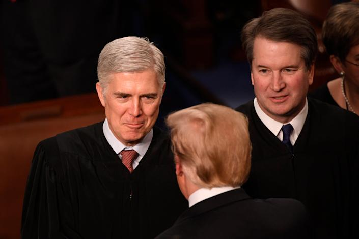 Supreme Court Associate Justices Neil Gorsuch, left, and Brett Kavanaugh greet President Donald Trump at a State of the Union address.