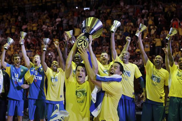 Maccabi of Tel Aviv captain Maccabi Guy Pnini, right, and his teammate Maccabi Tel Aviv's Alex Tyus hold the trophy as they celebrate with teammates after winning the Euroleague Final Four final against Real Madrid in Milan, Italy, Sunday, May 18, 2014. Maccabi won 98-86. (AP Photo/Luca Bruno)