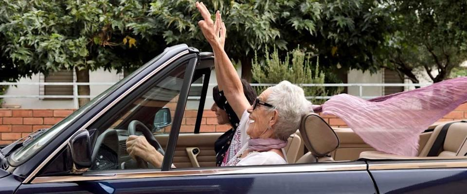 an older woman and a young woman driving a convertible