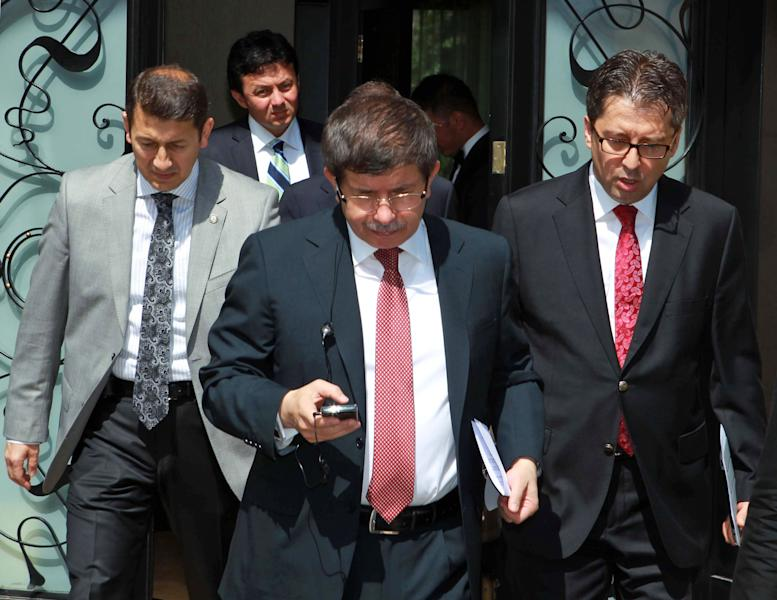 """In this image made available by the Turkish Foreign Ministry, Turkish Foreign Minister Ahmet Davutoglu, center, walks with advisors before an interview with the state-run TRT Television in Ankara, Turkey, Sunday, June 24, 2012. Davutoglu told State TV that Turkey would seek the meeting over article 4 of the NATO charter concerning Friday's incident. The article says member countries """"will consult together whenever, in the opinion of any of them, the territorial integrity, political independence or security of any of the parties is threatened."""" Davutoglu said Sunday that the jet was downed in international airspace after it mistakenly entered Syria, but the plane was not on a spying mission.(AP Photo/Hakan Goktepe, Turkish Foreign Ministry, HO)"""