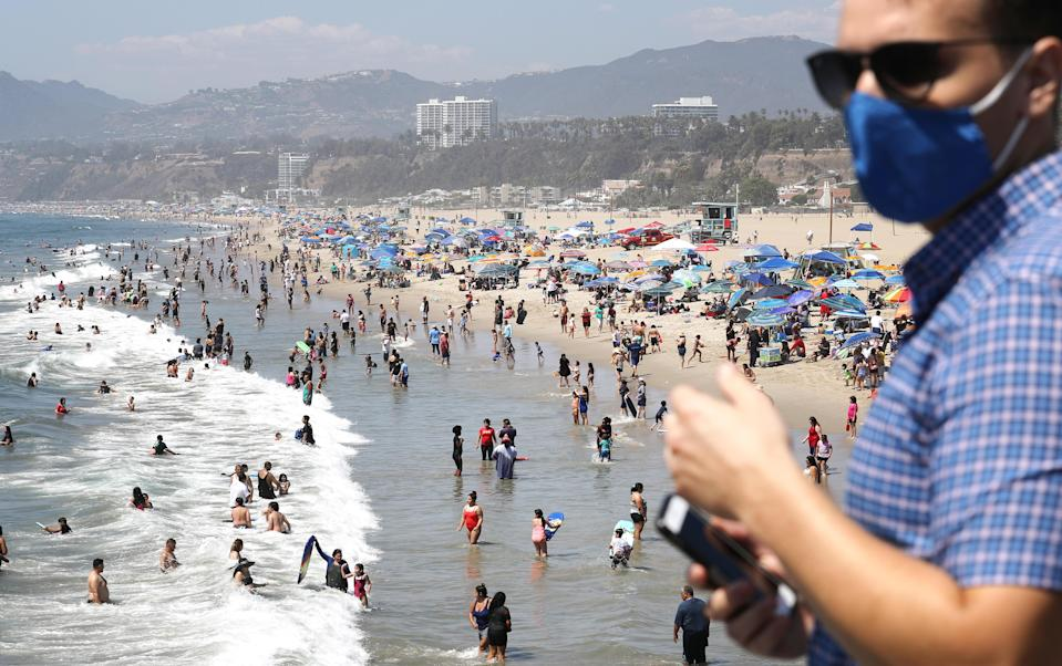 People gather on the beach at the Pacific Ocean on the first day of the Labor Day weekend amid a heatwave on September 5, 2020 in Santa Monica, California. Temperatures are soaring across California sparking concerns that crowded beaches could allow for wider spread of the coronavirus amid the COVID-19 pandemic. / Credit: Mario Tama  / Getty Images