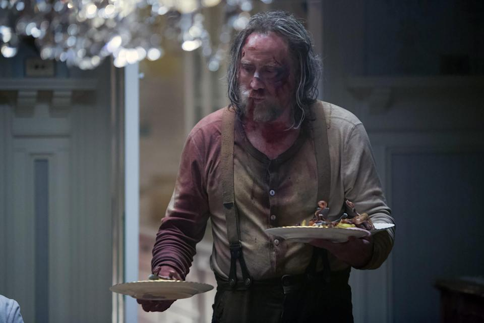 A bloodied Nicolas Cage holds two plates