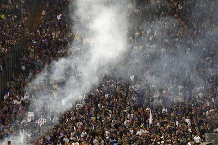 Supporters are seen behind smoke from flares before the Italian Cup final soccer match between Fiorentina and Napoli at the Olympic stadium in Rome May 3, 2014. REUTERS/Giampiero Sposito