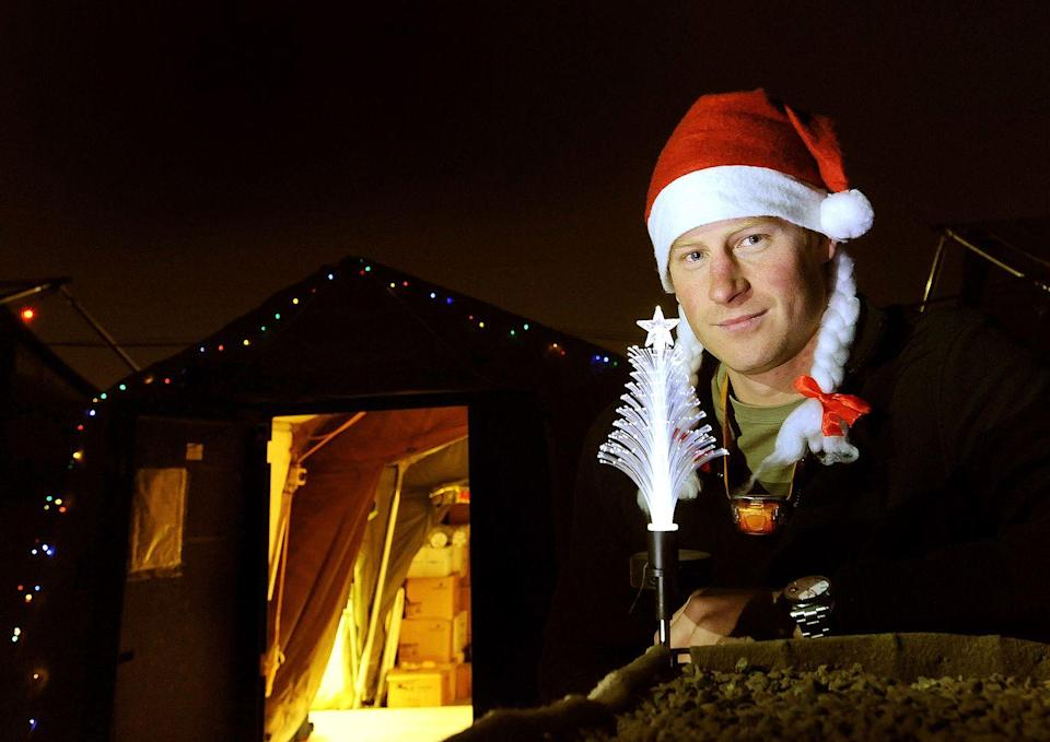 <p>Prince Harry poses with a small tree and Christmas hat at Camp Bastion on December 12, 2012 in Afghanistan. </p>