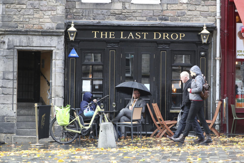 People drink outside the Last Drop pub as temporary restrictions announced by First Minister Nicola Sturgeon to help curb the spread of coronavirus will come into effect from 6pm, in Edinburgh, Friday, Oct. 9, 2020. (Andrew Milligan/PA via AP)