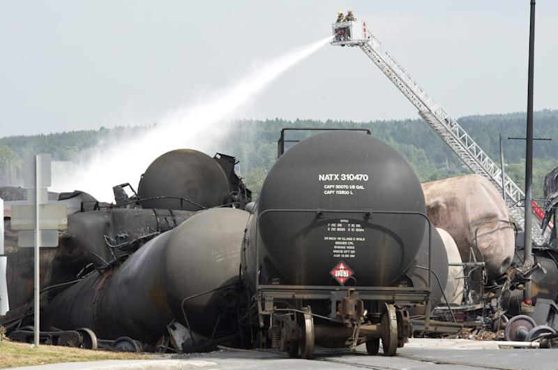 FILE - This July 7, 2013 file photo shows firefighters watering railway cars the day after a train derailed causing explosions of railway cars carrying crude oil in Lac Megantic, Que. The Obama administration has delayed by nearly a year a plan to boost safety standards for the type of rail car involved in a fiery explosion that killed at least 47 people in Canada this month. Officials began work on the rule more than a year before an oil train derailed and exploded in Quebec July 6, but the rule was never published. (AP Photo/The Canadian Press, Paul Chiasson, File)