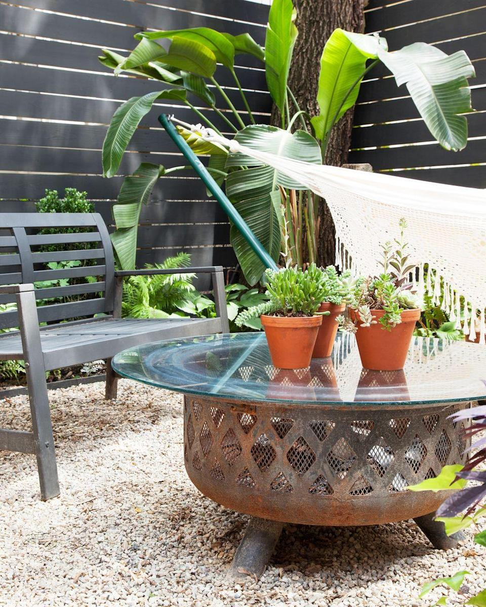 "<p>A table that turns into a fire pit is the perfect space-saving solution. Designer <a href=""http://meganpflugdesigns.com/2016/05/20/2016517o04lc8zdsxgj2mlyaeotbodo2lutrq/"" rel=""nofollow noopener"" target=""_blank"" data-ylk=""slk:Megan Pflug"" class=""link rapid-noclick-resp"">Megan Pflug</a> simply placed a glass top she found at a flea market on this fire pit to avoid squeezing a coffee table and pit into her limited backyard space.<br></p>"