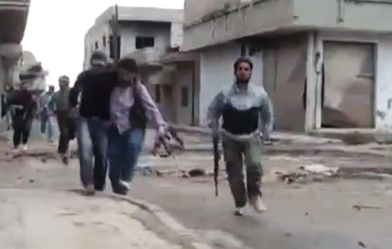 In this image made from amateur video released by the Shaam News Network and accessed Monday, May 14, 2012, purports to show a Syrian rebel helping an injured man in Rastan, Homs, Syria. Syrian troops shelled the rebel-held town, sparking intense clashes that sent bloodied victims flooding into hospitals and clinics, activists said. The violence around the country is eroding an internationally brokered peace plan that many observers see as the last hope to calm the 14-month-old crisis. (AP Photo/Shaam News Network via AP video) TV OUT, THE ASSOCIATED PRESS CANNOT INDEPENDENTLY VERIFY THE CONTENT, DATE, LOCATION OR AUTHENTICITY OF THIS MATERIAL