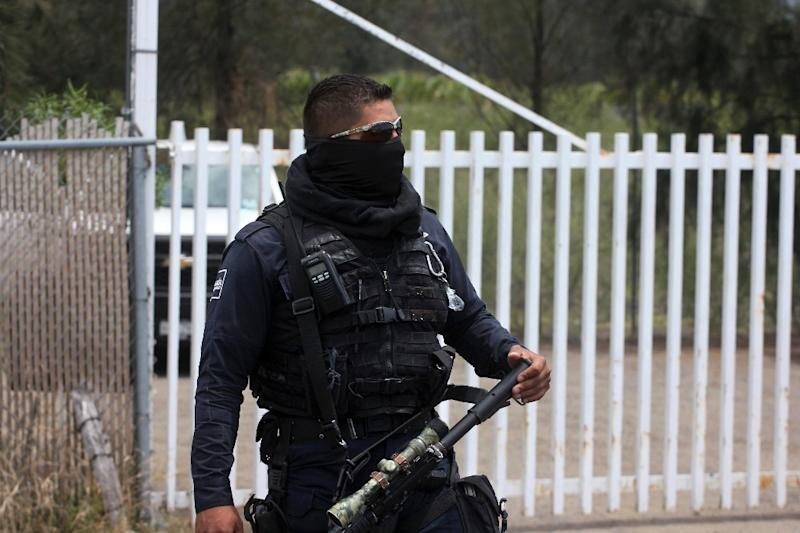 A Federal police officer stands guard outside a ranch where gunmen took cover during an intense gun battle with the police, along the Jalisco-Michoacan highway in Vista Hermosa, Michoacan State, on May 22, 2015 (AFP Photo/Hector Guerrero)