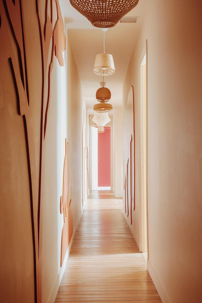 This corridor, with a row of IKEA hanging lamps, leads to the playroom.