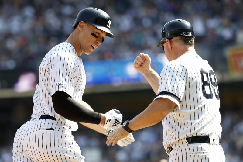 New York Yankees' Aaron Judge, left, celebrates with third base coach Phil Nevin (88) after hitting a home run against the Toronto Blue Jays during the first inning of a baseball game, Sunday, Sept. 22, 2019, in New York. (AP Photo/Michael Owens)
