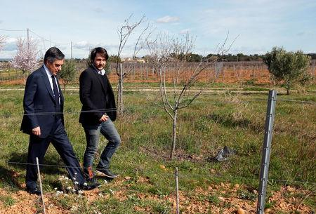 Francois Fillon, former French prime minister, member of the Republicans political party and 2017 presidential election candidate of the French centre-right walks in vineyards with a winegrower in Nimes, France, March 2, 2017.  REUTERS/Jean-Paul Pelissier