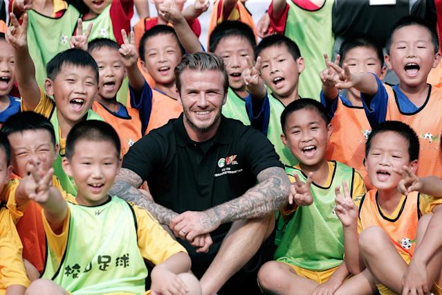 BEIJING, CHINA - JUNE 18: David Beckham poses with young fans at Nanjing Olympic Sports Center on June 18, 2013 in Nanjing, Jiangsu Province of China. (Photo by Lintao Zhang/Getty Images)