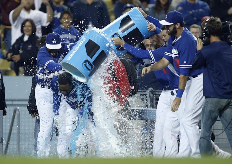 Los Angeles Dodgers' Darnell Sweeney is doused by teammates after hitting a walk off single to score Trayvon Robinson against the Los Angeles Angels during the 10th inning of an exhibition baseball game in Los Angeles, Friday, March 28, 2014. The Dodgers won 5-4. (AP Photo/Danny Moloshok)