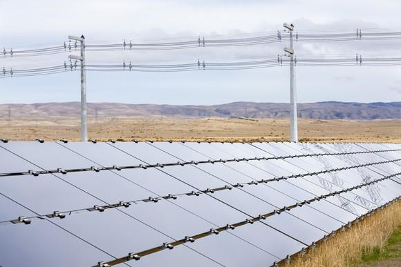 Row of solar panels in an arid open landscape with transmission lines right behind the array.