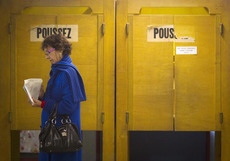 A Swiss woman leaves a polling booth at a polling station in the center of Geneva, Switzerland, Sunday, Oct 23, 2011. Swiss citizens voting in national elections Sunday were poised to hand nationalists an unprecedented 30 percent voice, following voting dominated by concerns about immigration, nuclear power and the economy. Word on booth door  is push.  (AP Photo/Anja Niedringhaus)