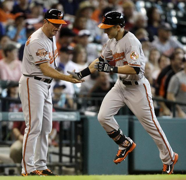 Baltimore Orioles' David Lough, right, is congratulated by third base coach Bobby Dickerson after hitting a home run during the second inning of a baseball game against the Houston Astros, Sunday, June 1, 2014, in Houston. (AP Photo/Patric Schneider)