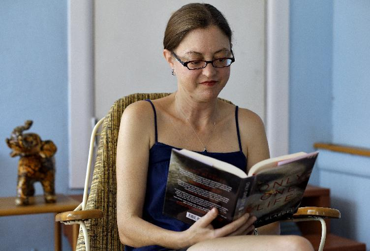 This photo taken Oct. 9, 2012 shows Erin Mitchell reading a book on her sun porch outside her home in St. Petersburg, Fla. Which way Florida swings in presidential elections is largely due to the transient nature of its population. A constant influx of new residents, like Mitchell, can make a difference from one election cycle to the next. Mitchell moved to Florida from Boston and had lived in Chicago before that. She used to be a Democrat, then registered as a Republican and is now an independent. She voted for Republican George W. Bush in 2000, but went for Democrats John Kerry in 2004 and Barack Obama in 2008. (AP Photo/Chris O'Meara)