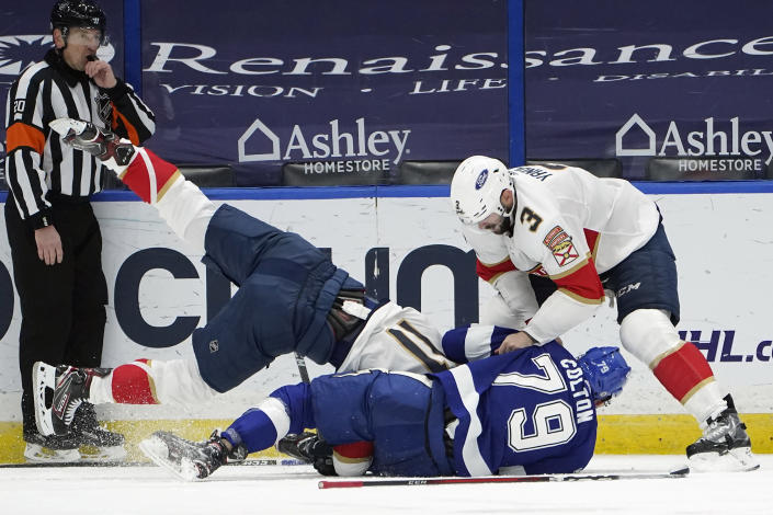 Tampa Bay Lightning left wing Ross Colton (79) takes down Florida Panthers left wing Jonathan Huberdeau (11) as defenseman Keith Yandle (3) gets involved during the third period of an NHL hockey game Sunday, March 21, 2021, in Tampa, Fla. Colton was penalized for roughing. (AP Photo/Chris O'Meara)