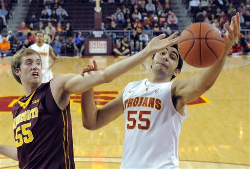 Minnesota's Elliott Eliason, left, and Southern California's Omar Oraby reach for a rebound during the first half of their NCAA basketball game, Saturday, Dec. 8, 2012, in Los Angeles. (AP Photo/Mark J. Terrill)