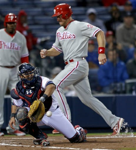 Atlanta Braves' Gerald Laird, left, catches a throw from the outfield as Philadelphia Phillies' Erik Kratz, right, scores off a sacrifice fly by Chase Utley, not pictured, in the second inning of a baseball game, Thursday, April 4, 2013, in Atlanta. (AP Photo/David Goldman)