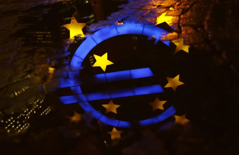 The famous euro sign landmark is reflected in a puddle outside the former headquarters of the European Central Bank (ECB) in Frankfurt