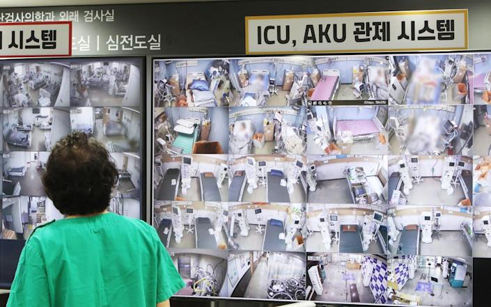 A medical worker looks at a screen showing negative pressure quarantine rooms at Bagae Hospital where patients infected with Covid-19 are treated - YONHAP/EPA-EFE/Shutterstock