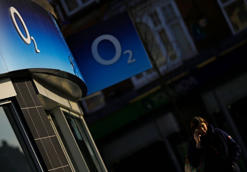 FILE PHOTO: A woman speaks on her mobile telephone outside an O2 shop in Loughborough