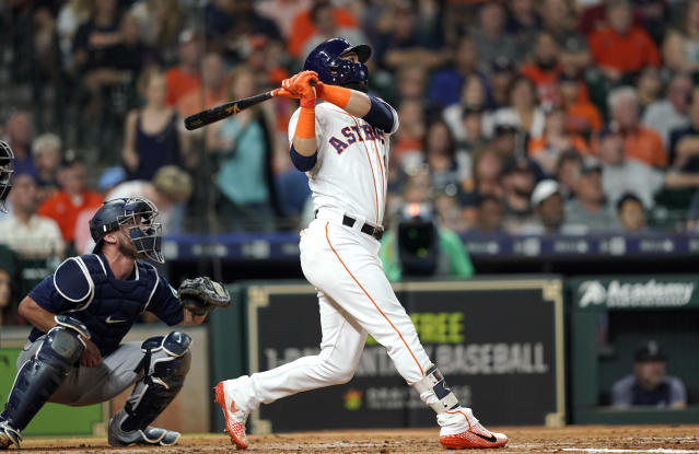 Houston Astros' Marwin Gonzalez, right, hits a two-run home run as Seattle Mariners catcher Chris Herrmann watches during the third inning of a baseball game Tuesday, Sept. 18, 2018, in Houston. (AP Photo/David J. Phillip)