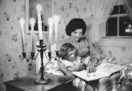 <p>Jackie Kennedy reads to her daughter Caroline in the bedroom of their summer home.</p>