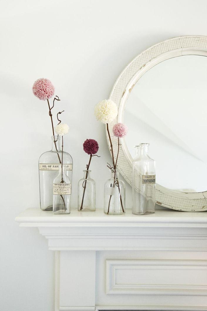 <p>Give yarn an opportunity to bloom. Crafter Lauren De Bellis came up with this genius way to keep vases stocked with fresh flowers—even in winter. The key to creating these allium-like blossoms: pom-pom makers in three different sizes.</p><p> Wrap yarn around the tool's arms, then follow the package instructions to make your own buds. Add a dab of hot glue to the end of a thin twig and insert into each pom-pom's center. Hold in place until the glue dries (about 10 seconds) and arrange.</p>