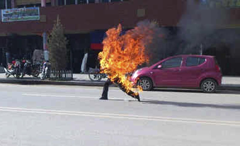 FILE - In this Oct. 23, 2012 file photo released by London-based rights group Freetibet.org, Dorje Rinchen, a farmer in his late 50s, runs after setting himself on fire on the main street in Xiahe, in northwestern China's Gansu province. A surge in self-immolations and large demonstrations by Tibetans in western China mark a new phase in protests against rule by the authoritarian Chinese government. (AP Photo/Freetibet.org, File) EDITORIAL USE ONLY, NO SALES