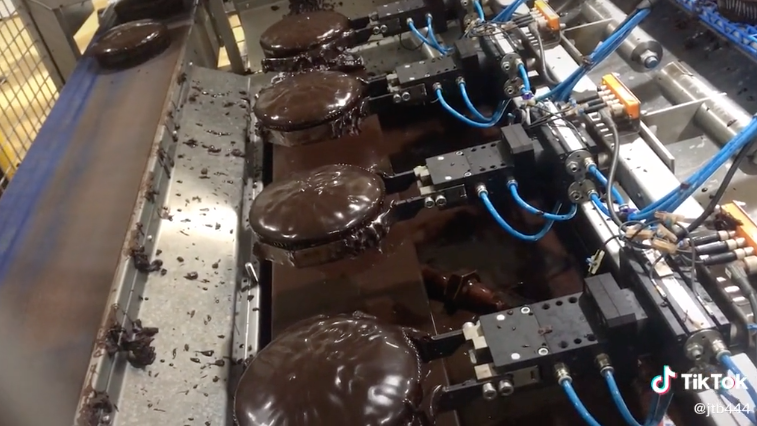 A row of Woolies mud cakes are seen being dunked in icing by robotic arms. Photo: TikTok/foodfactoryaus.