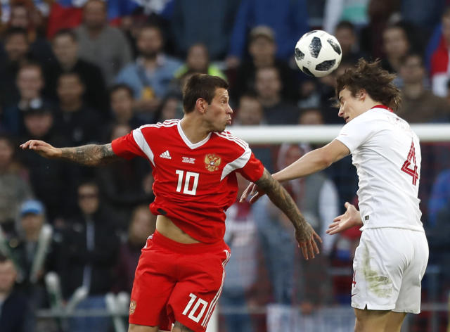 Russia's Fyodor Smolov, left, jumps for the ball with Turkey's Caglar Soyuncu during a friendly soccer match between Russia and Turkey at the VEB Arena stadium in Moscow, Russia, Tuesday, June 5, 2018. (AP Photo/Pavel Golovkin)