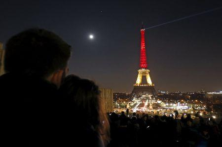 A couple looks at the Eiffel Tower lit up in the colours of the Belgian flag in tribute to the victims of today's bomb attacks in Brussels, in Paris, France, March 22, 2016. REUTERS/Philippe Wojazer