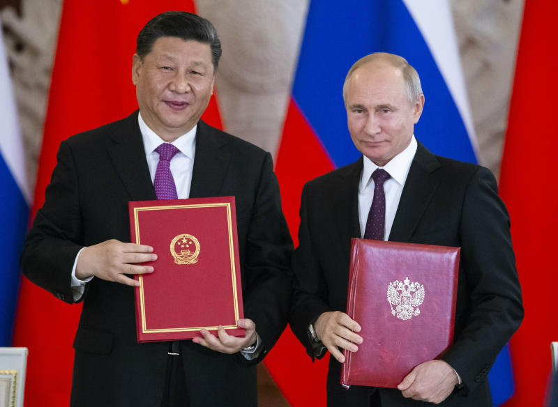 FILE - In this June 5, 2019 file photo, Russian President Vladimir Putin, right, and Chinese President Xi Jinping exchange documents during a signing ceremony following their talks in the Kremlin in Moscow, Russia. From nukes to huge food aid shipments to a shared skepticism about the United States, Chinese President Xi and North Korean leader Kim Jong Un will have a long list of topics to discuss when Xi heads north Thursday, June 20. (AP Photo/Alexander Zemlianichenko, Pool, File)