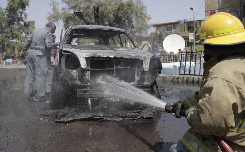Afghan security forces investigate the scene of an explosion while a firefighter douses a vehicle in front of Governor House in Jalalabad, east of Kabul, Afghanistan, Sunday, Sept 1, 2013. A bomb attached to a vehicle of the Jalalabad mayor exploded on Sunday, apparently targeting the mayor of the eastern city of Jalalabad, but wounded his driver instead. (AP Photo/Rahmat Gul)