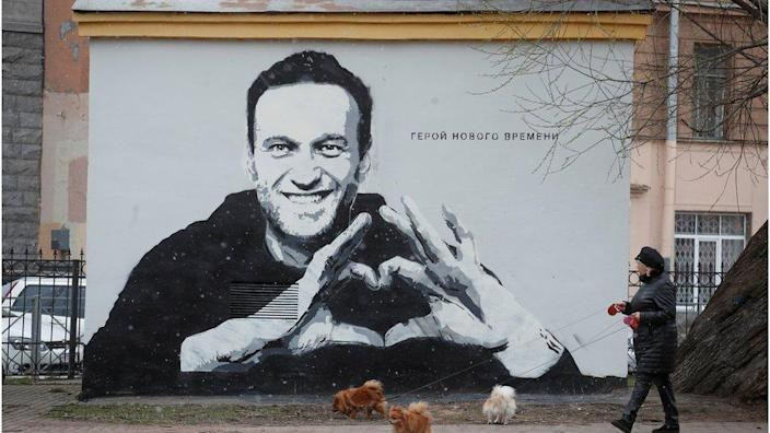 A woman walks her dogs in front of a graffiti depicting jailed Russian opposition politician Alexei Navalny in Saint Petersburg, Russia April 28, 2021